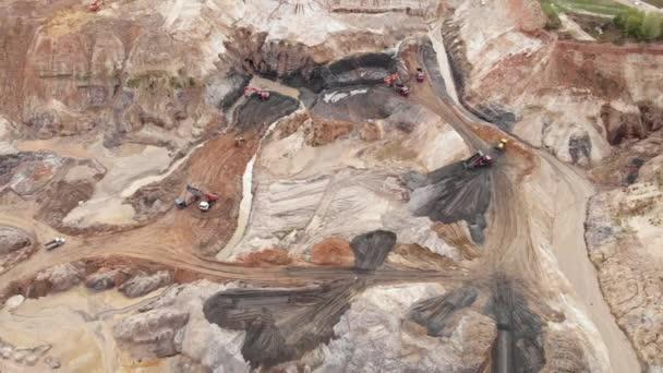 Tiefe riesige Bergbaugruben mit riesigen Mineralienbergen. Bagger verladen Eisenerz im Steinbruch. Bergbauausrüstung im Sand oder Steinbruch. Bergbau. Gewinnung von Kupfer und Gips