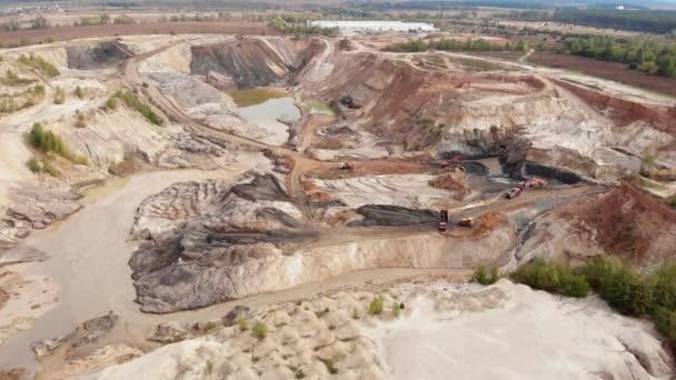 Riesiger industrieller Steinbruch zur Förderung von Eisenerz, Ton, Steinen und Mineralien. Maschinenwagen und Bagger arbeiten im großen produzierenden Steinbruch. Bergbau