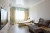 Tágas hálószoba belső nagy kanapé és ágy, és fényes szakaszon mennyezet