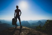 Successful young woman hiker standing on sunrise mountain peak cliff edge