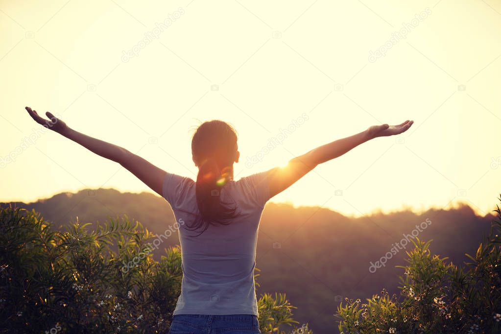 freedom woman raised arms to sunrise on mountain top in the morning
