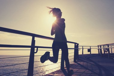 sporty young fitness woman running on coast