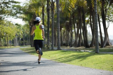 sporty young fitness woman running at tropical park