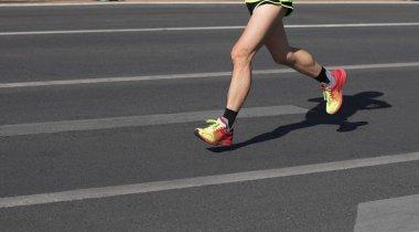marathon runners legs running on city road