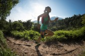 Photo Determined woman trail runner running in morning forest