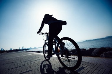silhouette of cyclist riding bike in the sunrise coast road