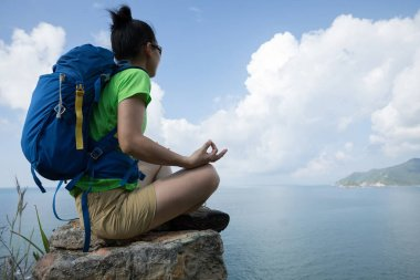Successful woman hiker meditating on mountain top cliff edge