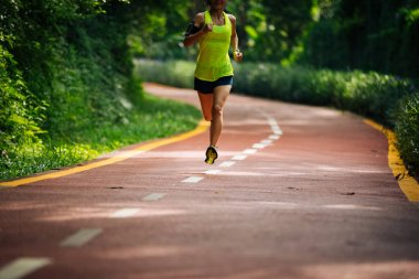 Healthy woman runner running on morning park road