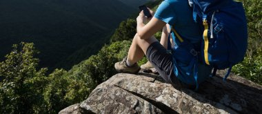 Woman hiker using smartphone on mountain cliff edge