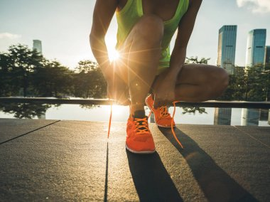 Fitness woman runner tying shoelace before running on city