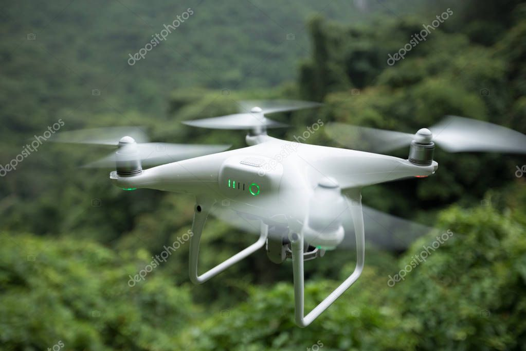 White drone with camera flying over tropical forest