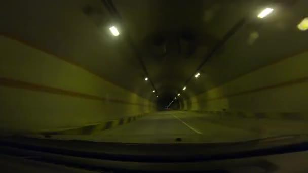 Blick durch die Windschutzscheibe eines Autos, das sich auf einem dunklen Tunnel bewegt
