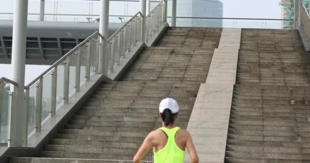 Fiatal nő kocog fel a városi lépcsőn