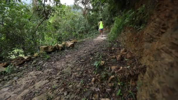Young female athlete running on tropical forest trail