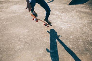 Skateboarder doing ollie at skatepark at summer