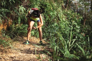 Young woman trail runner taking rest and checking time while running on tropical forest trail