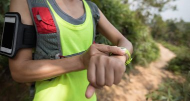 Asian woman setting the sports watch before trail running on mountain