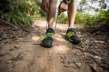 Young woman trail runner tying shoelace while running on tropical forest trail