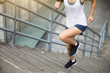 Young woman runner sportswoman running up city stairs