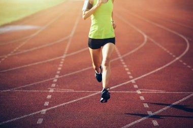 Fitness sportswoman running on stadium race tracks