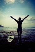 Šťastná žena svoboda surfař vztaženýma rukama dosáhnout nebe za úsvitu na útesu u moře