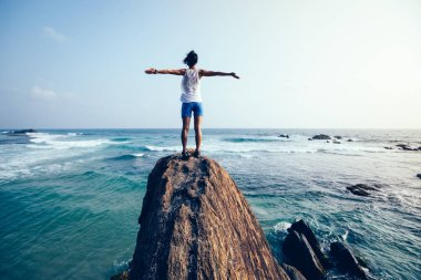 Freedom young woman with outstretched arms standing on seaside rock