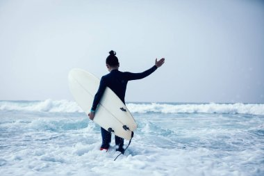 Woman surfer with surfboard going to surf the big waves