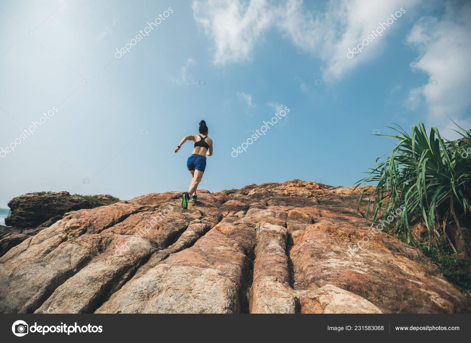 9ae08f3ddbf Corredor de trail de mujer corriendo a la cima de la montaña rocosa en la  costa– Imagen de Archivo