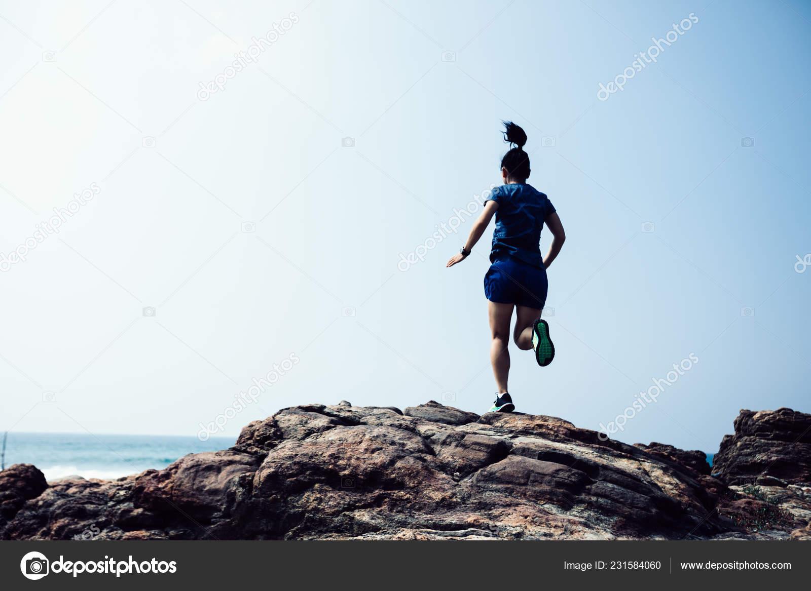 3082916f4e0 Corredor de trail de mujer corriendo a la cima de la montaña rocosa en la  costa– imagen de stock
