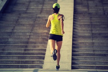 Young woman runner running up on city stairs, jogging and running in urban training workout