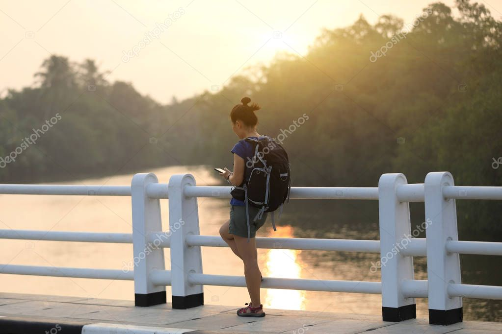 Tourist stand on bridge over the sunset river and using mobile phone