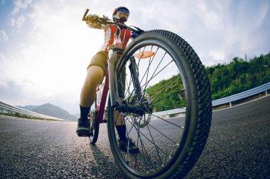 Woman cyclist riding bike on highway