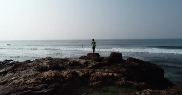 mladý zdravý životní styl žena, která běží na skalnaté pláži