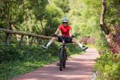 Žena cyklistka na koni horské kolo venku v lese