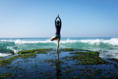 Woman practice yoga at seaside cliff edge facing coming strong sea waves