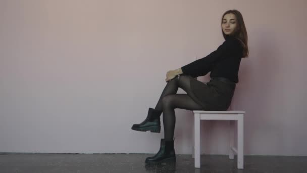 girl sitting on a chair and standing next to a chair on a white gray background