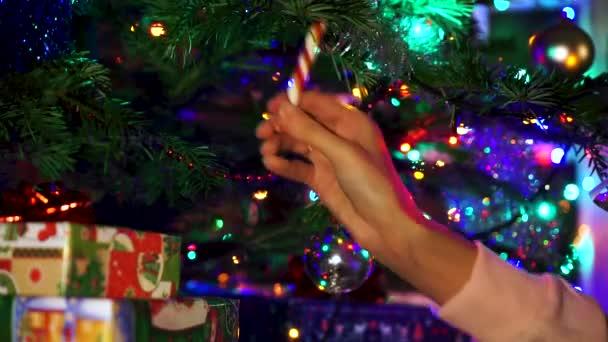 Ruční žena dekorace na vánoční stromeček s vánoční záře světel.