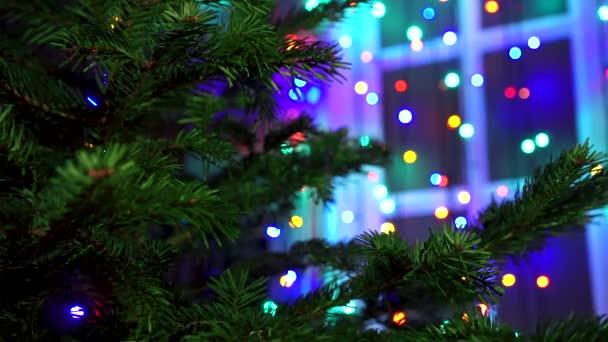 Hand man decorating on Christmas tree with Christmas glow lights.