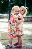 Two toddlers sisters hugging in park
