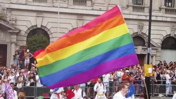 LONDON, UK - July 6th 2019: People wave LGBTQ gay pride flags at a solidarity march