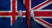 Obchodník stojí na popraskané vlajce Velké Británie a Islandu. Politický koncept