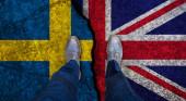 Obchodník stojící na popraskané vlajce Velké Británie a Švédska. Politický koncept