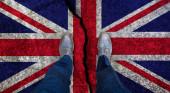Obchodník stojí na popraskané vlajce Spojeného království. Koncept brexitu
