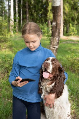 A young girl shows something to her dog in a mobile phone. A child plays with a dog and telephone