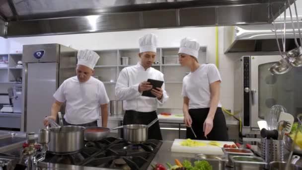 rušné kuchařů a kuchyň kuchař poradenství s tabletem