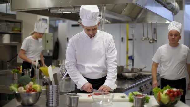 Šéfkuchař připravuje salát kuchaři pomáhají