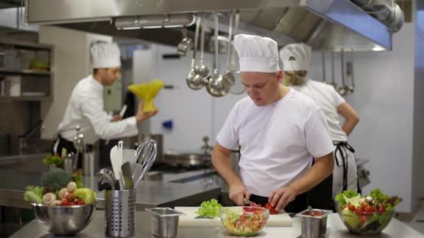 Šéfkuchař připravuje salát pak bolí rameno zranění