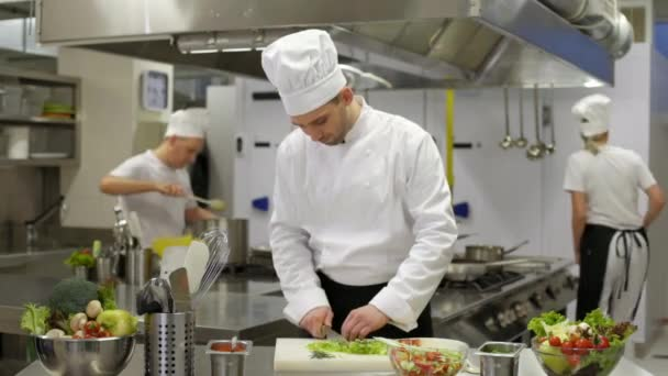 Koch bereitet Salat zu und verletzt sich dann am Handgelenk