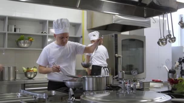Chef pohnutí polévka v hrnci kuchaři pomáhají dělat salát