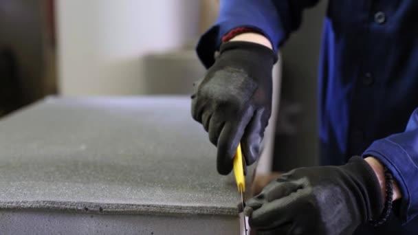 Detailní záběr mladého muže v továrně na nábytek, který výpalky přebytečné pěny z pohovky. Proces výroby nábytku. Mladý muž v tmavé srsti, který snížení přebytečné části pohovky na pracovní stůl.